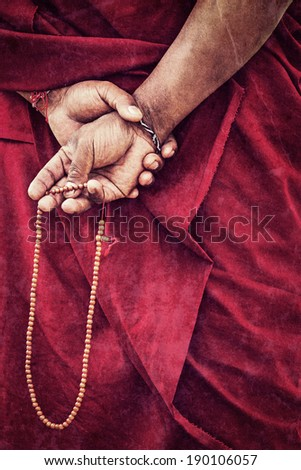 Vintage retro effect filtered hipster style travel image of Tibetan Buddhism - prayer beads in Buddhist monk hands with grunge texture overlaid. Ladakh, India - stock photo