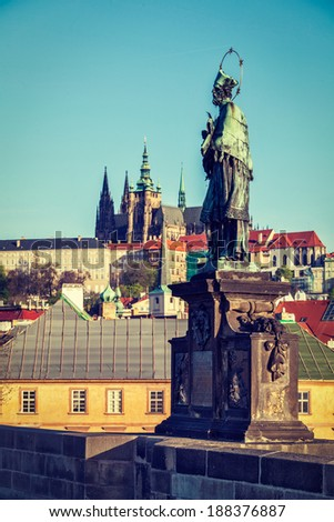 Vintage retro hipster style travel image of John of Nepomuk national saint of the Czech Republic statue on Charles Brigde at site where saint was thrown into Vltava with St. Vitus Cathedral in Prague - stock photo