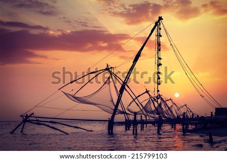 Vintage retro hipster style travel image of Kochi chinese fishnets on sunset. Fort Kochin, Kochi, Kerala, India - stock photo