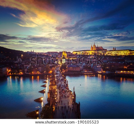 Vintage retro hipster style travel image of night aerial view of Prague castle and Charles Bridge over Vltava river in Prague, Czech Republic. Prague, Czech Republic - stock photo