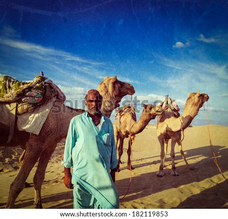 Vintage retro hipster style travel image of Rajasthan travel background Indian man cameleer (camel driver) portrait with camels in Thar desert with grunge texture overlaid. Jaisalmer, Rajasthan, India - stock photo