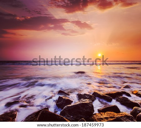 Vintage retro hipster style travel image of tropical beach vacation background - waves and rocks on beach on sunset with beautiful cloudscape - stock photo
