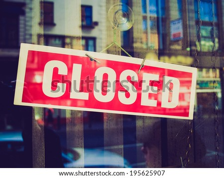 Vintage retro looking Closed sign in a shop showroom with reflections - stock photo