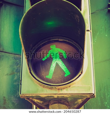 Vintage retro looking Green light on a pedestrian traffic light - stock photo