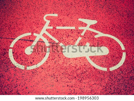 Vintage retro looking Stencil bike sign on a bicycle lane - stock photo