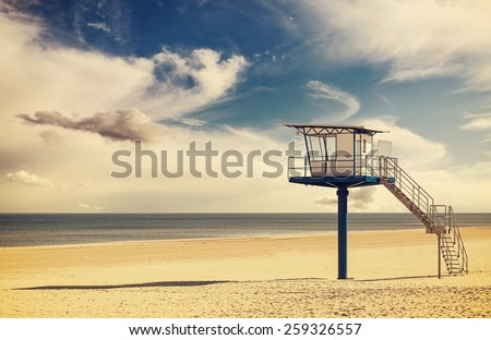 Vintage retro style filtered picture of a lifeguard tower on a beach. - stock photo