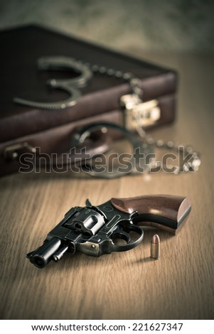 Vintage revolver and bullet with briefcase and handcuffs on background. - stock photo