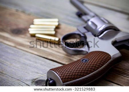 vintage revolver nagant with ammunition on an old wooden surface - stock photo