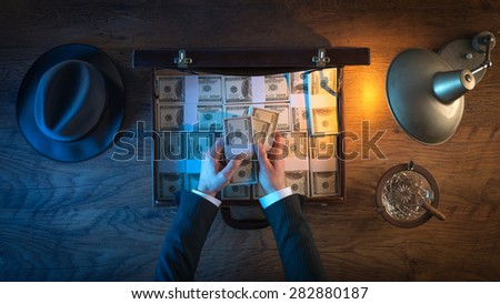 Vintage rich businessman's desk with a briefcase filled with dollar packs, he is counting paper currency - stock photo