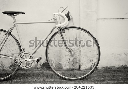Vintage road bicycle leaning on white wall - stock photo