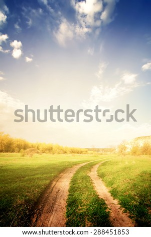 vintage road through fields with green grass and blue sky with clouds, natural background - stock photo