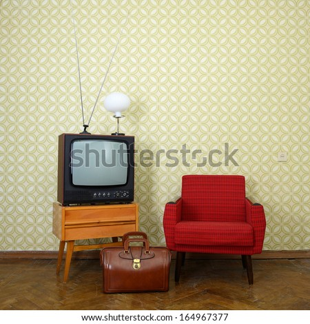 Vintage room with old fashioned armchair, retro tv, lamp and bag over obsolete wallpaper - stock photo