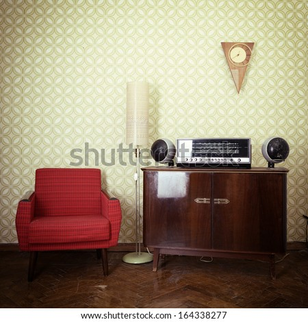 Vintage room with wallpaper, old fashioned armchair, retro player, loudspeakers, clocks and standart lamp, toned - stock photo