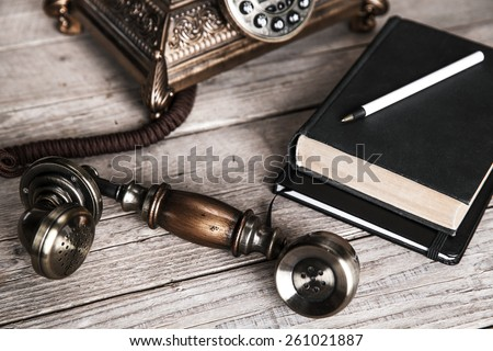 Vintage rotary telephone and old phone book on table near wall - stock photo