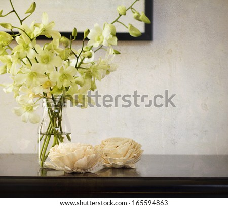 Vintage rustic texture behind orchids in glass vase - stock photo
