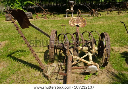 Vintage rusty grass cutting and harvesting agricultural machinery equipment. - stock photo