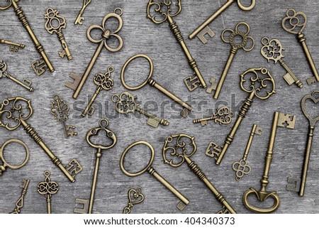 vintage rusty key on grunge wooden background - stock photo