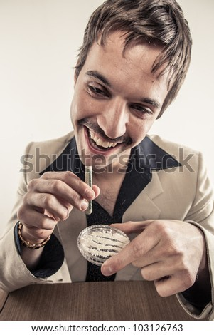 Vintage 1970's drug user doing coke looking high with rolled up dollar bill on plastic dish - stock photo