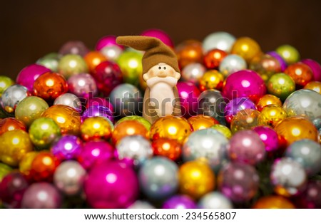 vintage Santa Claus figure between many colorful christmas baubles, christmas decoration  - stock photo