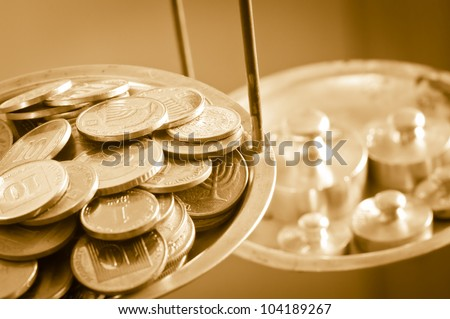 vintage scale weights outweigh coins on an old balance - stock photo