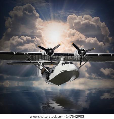 Vintage seaplane flying against sunset over sea.  - stock photo