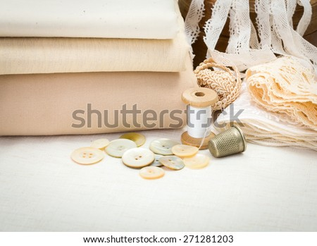Vintage sewing craft items: fabrics, laces, thread, thimble, shell buttons - stock photo