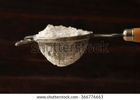 Vintage sieve filled with flour against rustic wood background.  Baking concept/ background. - stock photo