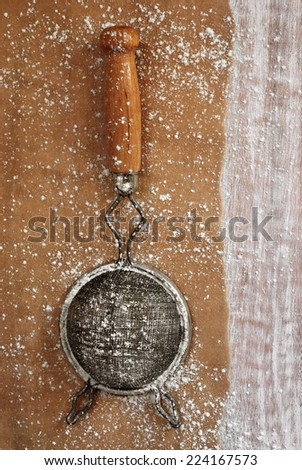 Vintage sieve on parchment paper with distressed wood as background.  Baking concept. - stock photo