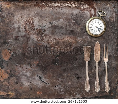 Vintage silver cutlery and antique pocket watch on rustic textured metal background. Antique tableware - stock photo