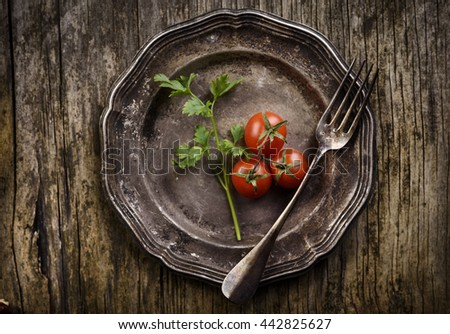 Vintage silver plate and fork on aged wooden background - stock photo