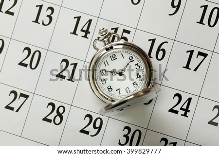 Vintage silver pocket watch laying on calender page with dates, top view - stock photo