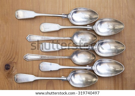 Vintage silver spoons on wooden background - stock photo
