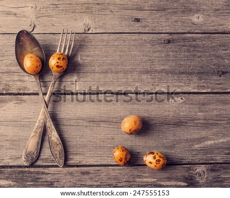 vintage silverware fork and spoon with easter quail eggs on old wooden background - stock photo