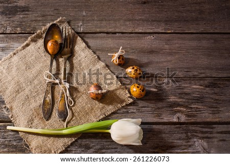 vintage silverware fork and spoon with easter quail eggs on old wooden table - stock photo