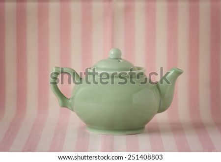 Vintage small green teapot in retro decor - stock photo
