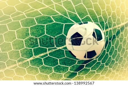 Vintage soccer ball in net, goal scroll, background - stock photo