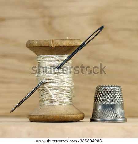 Vintage spool of thread with needle closeup on old wooden background. Tailor's work table, textile or fine cloth making. - stock photo