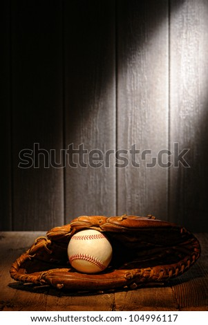 Vintage sport ball in an old baseball catcher leather glove on aged wood planks in an antique stadium dugout - stock photo