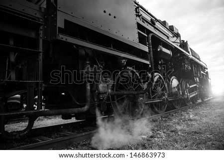 vintage steam locomotive heading towards sunset - black and white picture - stock photo