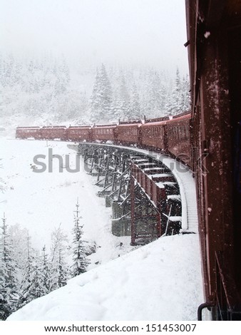 Vintage Steam Train in Snow over Trestle                                - stock photo