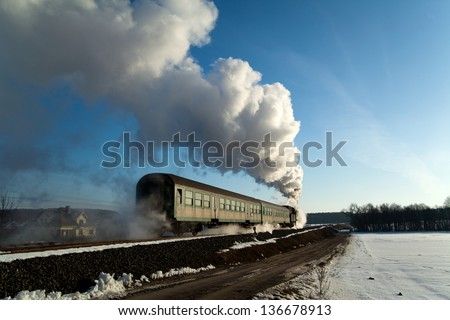 Vintage steam train puffing through countryside during wintertime  - stock photo