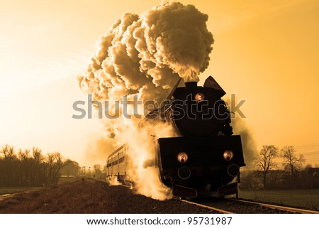 Vintage steam train starting from the station, wintertime - stock photo