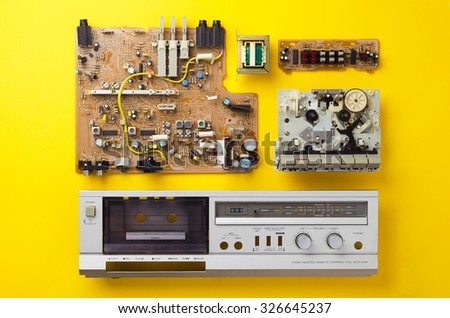 Vintage stereo cassette deck components well organized over yellow background, top view - stock photo
