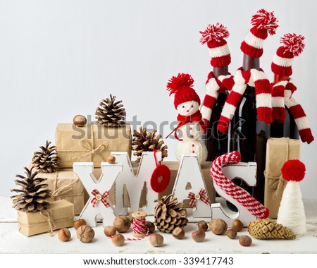 Vintage stile. Christmas card. Christmas decorations - letters XMAS, gifts, knitwear, nuts and bottles of wine in knitted hats. - stock photo