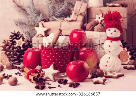 Vintage stile. Christmas decorations - cookies, apples, spices. Cozy rustic Christmas setting with a cup of hot chocolate with marshmallow  in a red knitted cup holder. - stock photo