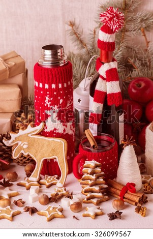 Vintage stile. Christmas decorations - cookies, apples, spices, mulled wine. Cozy rustic Christmas setting with a Cup of hot mulled wine in a red knitted Cup holder, thermos and jars for the cookies.  - stock photo