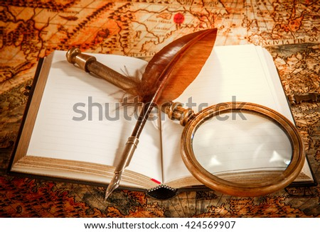 Vintage still life - magnifying glass, old book and goose quill pen lying on an old map in 1565. - stock photo