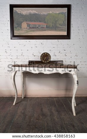 Vintage still life of an old retro desktop clock placed on a white vintage wooden table on background of white painted brick wall, hanged painting and dark wooden floor - stock photo