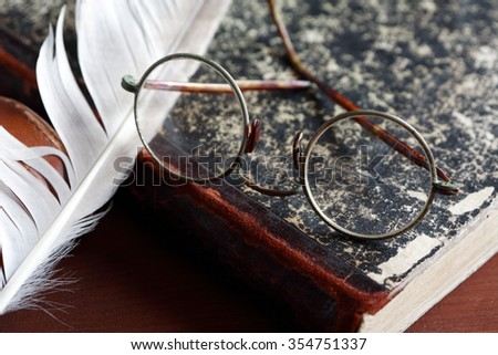 Vintage still life. Old spectacles on book near quill pen - stock photo