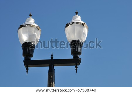 Vintage street lamp isolated against a blue sky background - stock photo